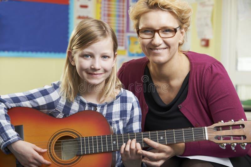 Δάσκαλος που βοηθά το μαθητή για να παίξει την κιθάρα στο μάθημα μουσικής στοκ εικόνες