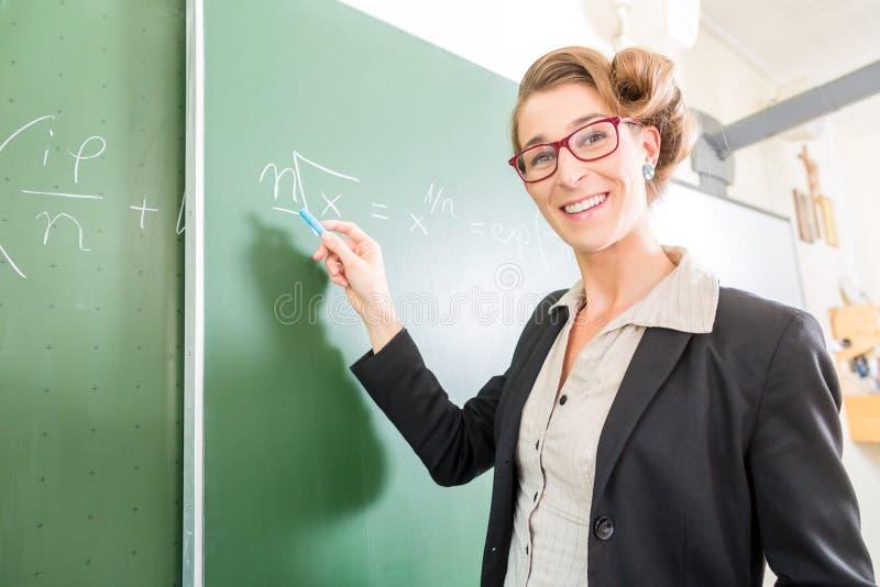 Δάσκαλος που γράφει με την κιμωλία μπροστά από τη σχολική τάξη εν πλω στοκ εικόνες