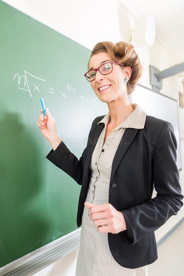 Δάσκαλος που γράφει με την κιμωλία μπροστά από τη σχολική τάξη εν πλω στοκ φωτογραφίες