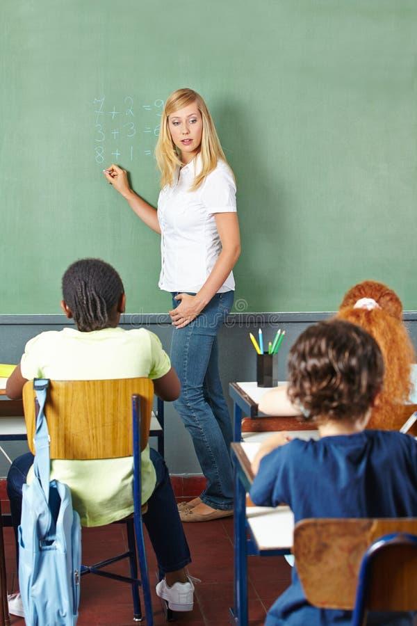 Δάσκαλος που γράφει στον πίνακα κιμωλίας στοκ εικόνες
