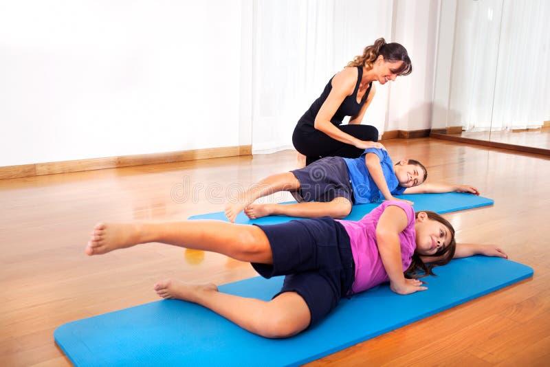 Δάσκαλος που εξηγεί τις νέες ασκήσεις ικανότητας αγοριών για να ισορροπήσει το σώμα στοκ εικόνα
