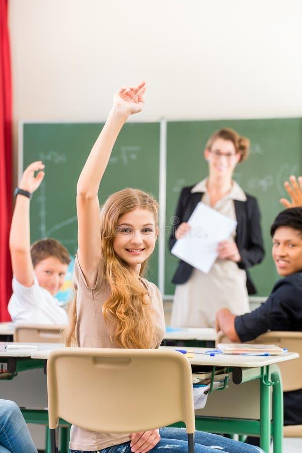 Δάσκαλος που διδάσκει μια κατηγορία μαθητών στο σχολείο στοκ φωτογραφίες
