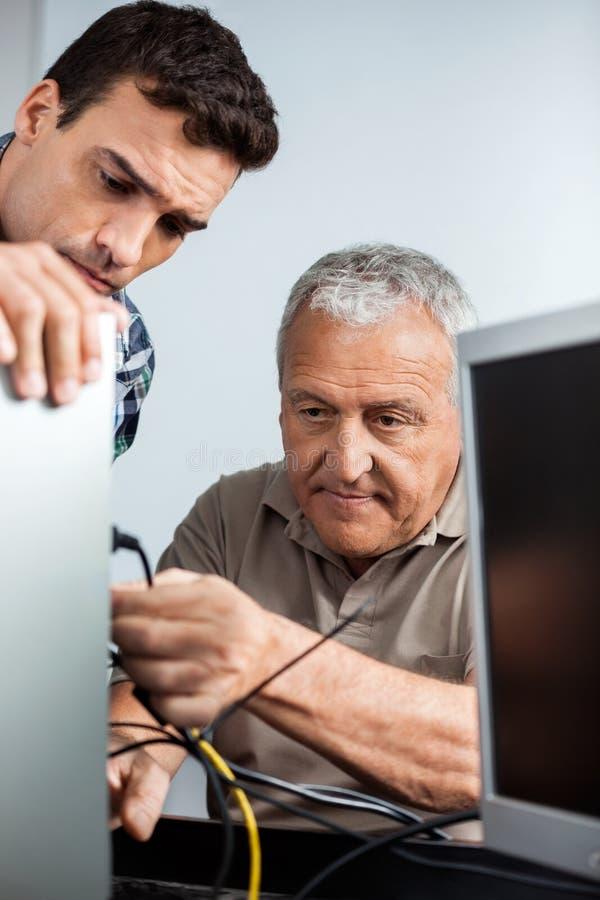 Δάσκαλος που προσέχει το ανώτερο άτομο τον υπολογιστή στοκ φωτογραφία με δικαίωμα ελεύθερης χρήσης