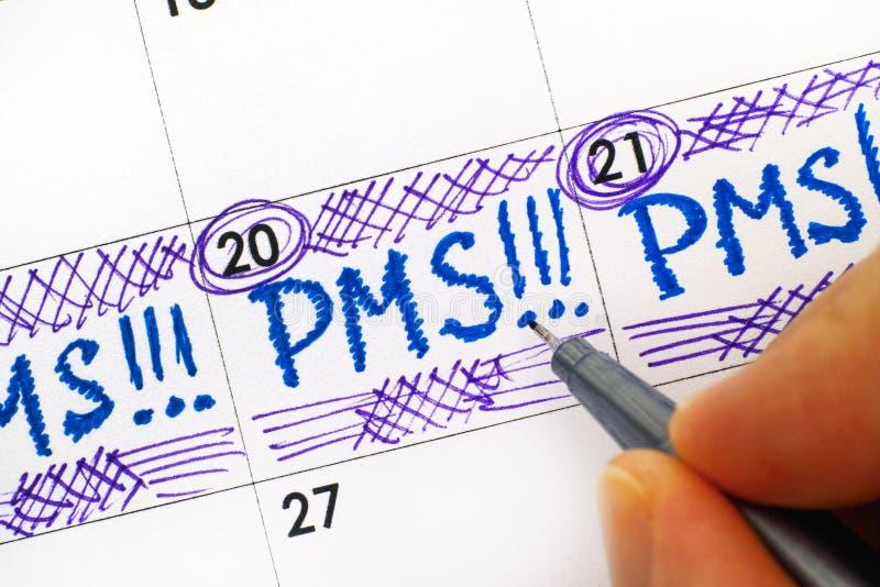 Δάχτυλα γυναικών με την υπενθύμιση PMS γραψίματος μανδρών στο ημερολόγιο στοκ εικόνες
