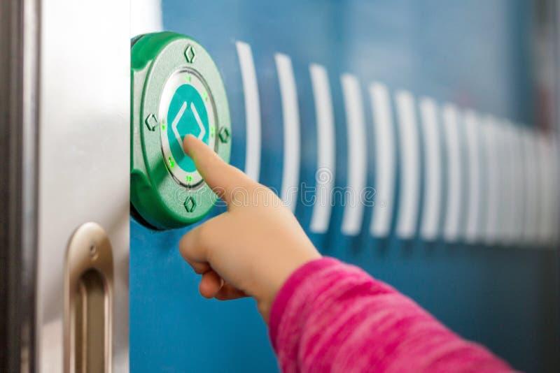 Δάχτυλο παιδιών που ωθεί το πράσινο στρογγυλό κουμπί αφής με τα βέλη Διαφανής πόρτα μεταξύ των μεταφορών στο intercity τραίνο Σύγ στοκ φωτογραφίες