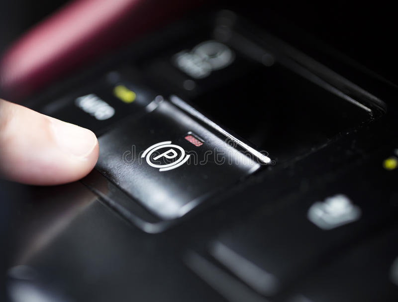 Δάχτυλο που πιέζει το ηλεκτρονικό κουμπί φρένων χώρων στάθμευσης στοκ εικόνες