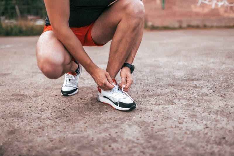 Δένοντας κορδόνια ατόμων αθλητών στα παπούτσια, κατάρτιση, ικανότητα workout που Υπόβαθρο θερινών πόλεων του αθλητικού τομέα στοκ εικόνα