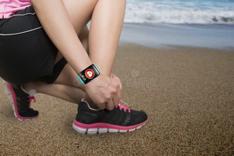 Δένοντας κορδόνια αθλητριών που φορούν το πνεύμα αισθητήρων υγείας smartwatch στοκ εικόνες
