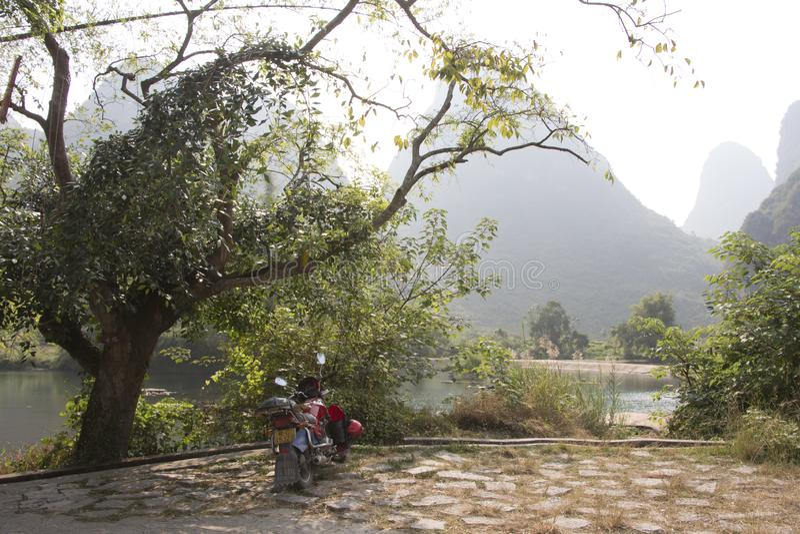 Δέντρα και μοτοσικλέτες Banyan από Yulong River σε Yangshuo, Κίνα στοκ φωτογραφίες