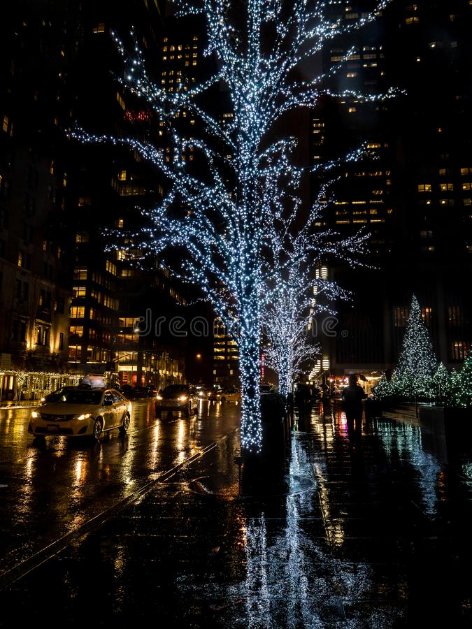 Δέντρο που καλύπτεται στα άσπρα φω'τα Χριστουγέννων που απεικονίζουν στο βροχερό έδαφος στη Νέα Υόρκη κατά τη διάρκεια των Χριστο στοκ φωτογραφία