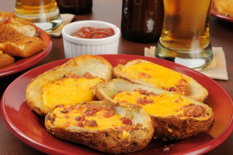 Δέρματα πατατών με το τυρί και το μπέϊκον τυριού Cheddar στοκ εικόνες