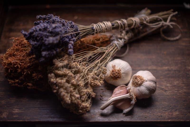 Δέσμες των ιατρικών χορταριών και των λουλουδιών με το σκόρδο Βοτανική ιατρική στοκ φωτογραφίες