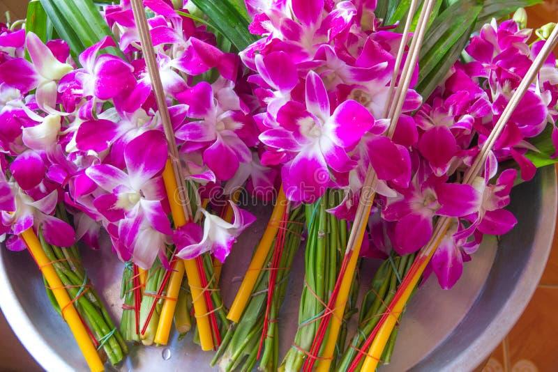 Δέσμες των λουλουδιών ορχιδεών με τα κεριά και των ραβδιών κινέζικων ειδώλων για τη λατρεία ο μοναχός στο ταϊλανδικό ύφος στοκ εικόνες