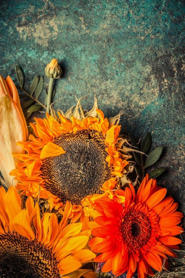 Δέσμη λουλουδιών φθινοπώρου με τους ηλίανθους στο σκοτεινό αγροτικό υπόβαθρο, τοπ άποψη στοκ φωτογραφία