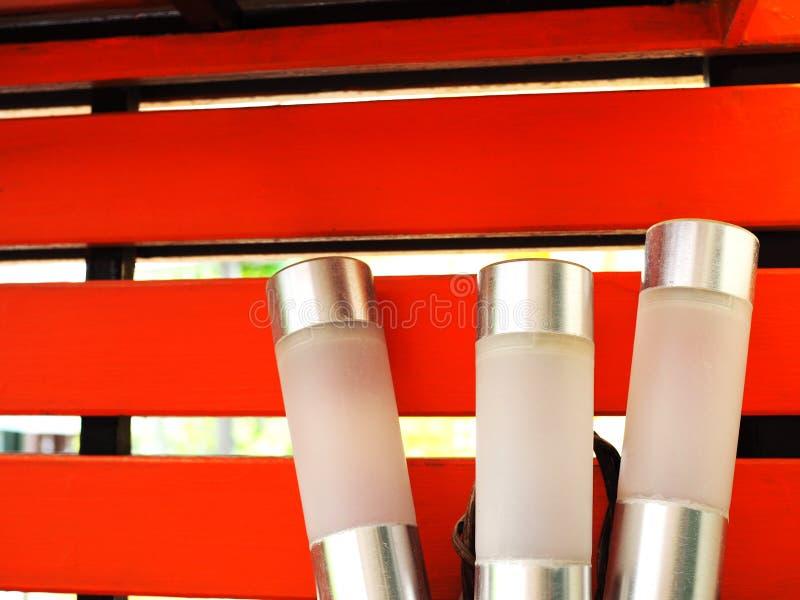 Δέσμη ραβδιών λαμπτήρων των ασημένιων άσπρων οδηγήσεων, κόκκινος ξύλινος τοίχος στοκ φωτογραφίες