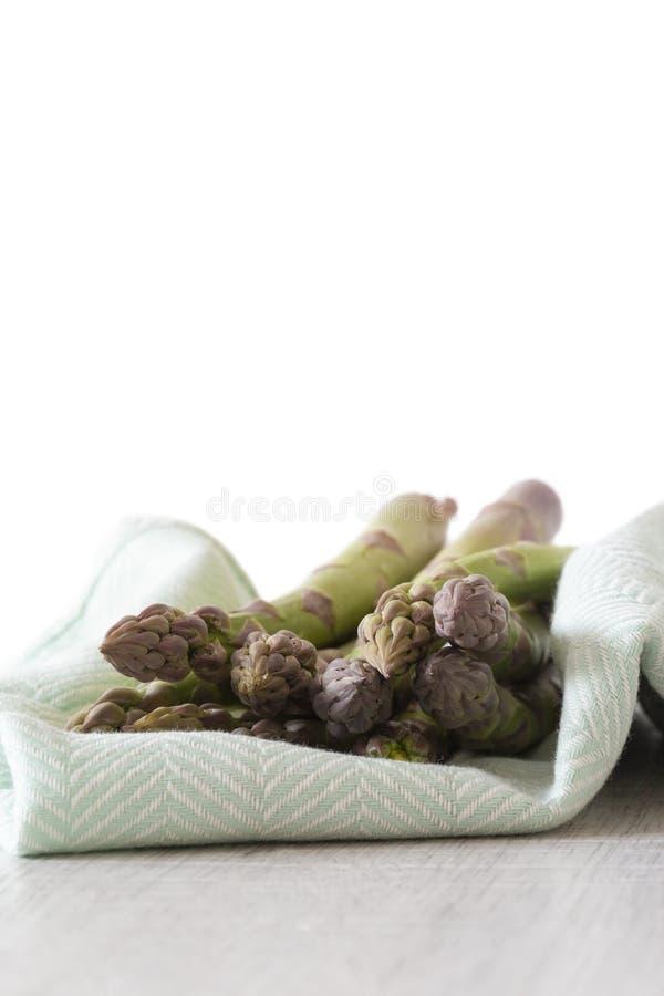 Δέσμη σπαραγγιού σε μια πράσινη πετσέτα τσαγιού στοκ φωτογραφία