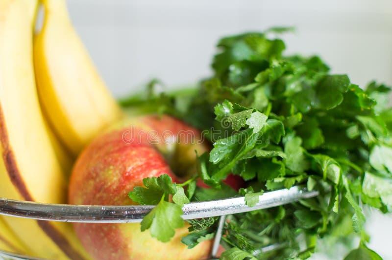 Δέσμη του φρέσκου πράσινου μαϊντανού με τα φρούτα στο κύπελλο φρούτων Συστατικά καταφερτζήδων στοκ εικόνα με δικαίωμα ελεύθερης χρήσης