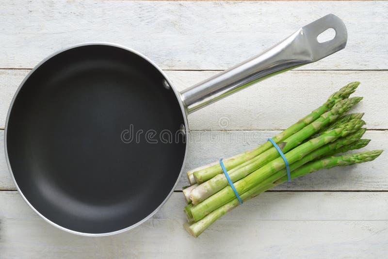 Δέσμη του φρέσκου σπαραγγιού δίπλα σε ένα τηγανίζοντας τηγάνι σε έναν άσπρο ξύλινο πίνακα στοκ φωτογραφία με δικαίωμα ελεύθερης χρήσης