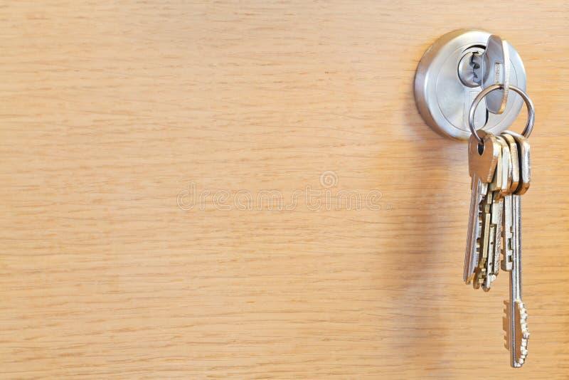 Δέσμη των εγχώριων κλειδιών στην κλειδαριά της ξύλινης πόρτας στοκ εικόνα