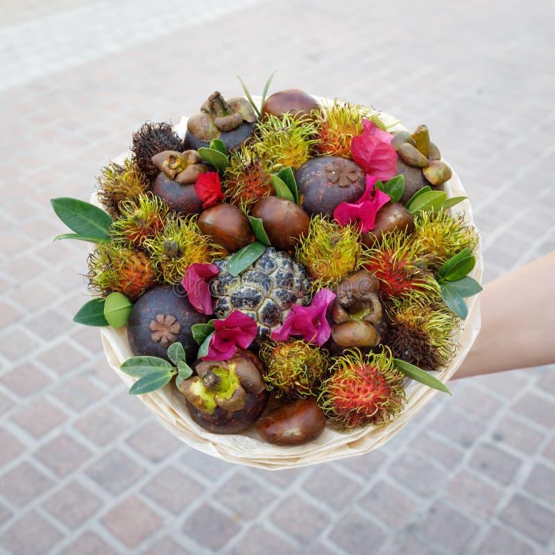 Δέσμη των εξωτικών φρούτων όπως rambutan, mangosteen, κάστανο σε ένα χέρι γυναικών στοκ φωτογραφία