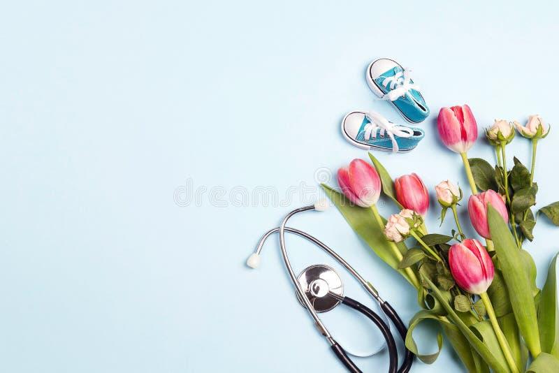 Δέσμη των τουλιπών με τα παπούτσια στηθοσκοπίων και μωρών στο μπλε υπόβαθρο r στοκ φωτογραφίες