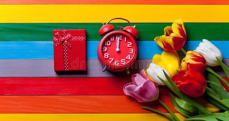 Δέσμη των τουλιπών, του κόκκινων ρολογιού και του δώρου που βρίσκονται στον πίνακα στοκ εικόνα με δικαίωμα ελεύθερης χρήσης