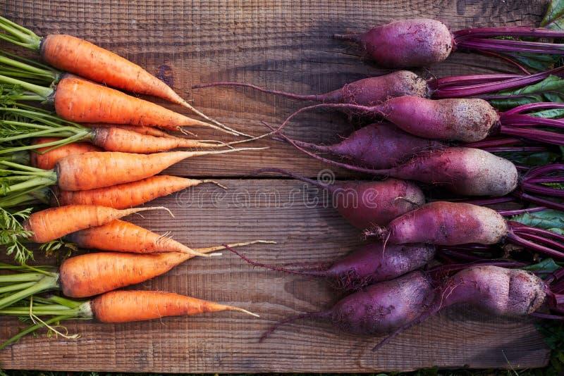 Δέσμη των φρέσκων οργανικών παντζαριών και των καρότων στον ξύλινο αγροτικό πίνακα Το καρότο βρίσκεται απέναντι από το τεύτλο στοκ εικόνες