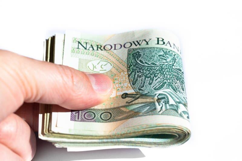 Δέσμη 100 zloty τραπεζογραμματίων στο χέρι ενός νεαρού άνδρα o στοκ εικόνα