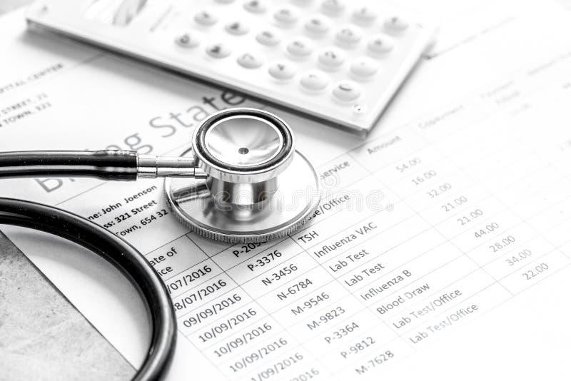 Δήλωση τιμολόγησης υγειονομικής περίθαλψης με το στηθοσκόπιο γιατρών ` s στην πέτρα στοκ εικόνα