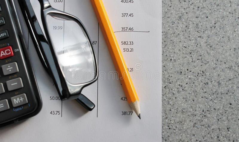 Δήλωση τράπεζας με τα γυαλιά και τον υπολογιστή μολυβιών στοκ φωτογραφίες