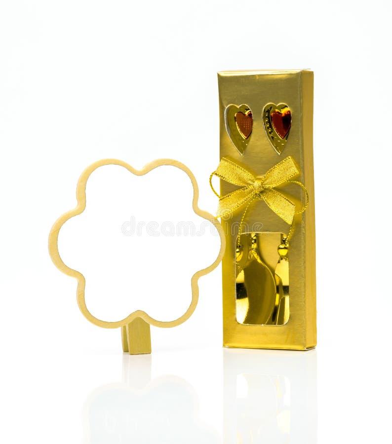 Δίκρανο και κουτάλι στα χρυσά μαχαιροπήρουνα κιβωτίων με τις διακοσμήσεις και whiteboard στοκ φωτογραφίες