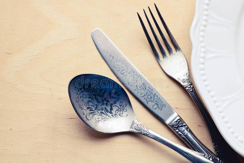 Δίκρανο και μαχαίρι κουταλιών κοντά στο άσπρο πιάτο Έννοια εστιατορίων στοκ φωτογραφία