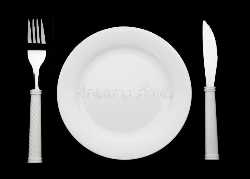Δίκρανο και πιάτο μαχαιριών σε ένα μαύρο υπόβαθρο στοκ εικόνα με δικαίωμα ελεύθερης χρήσης