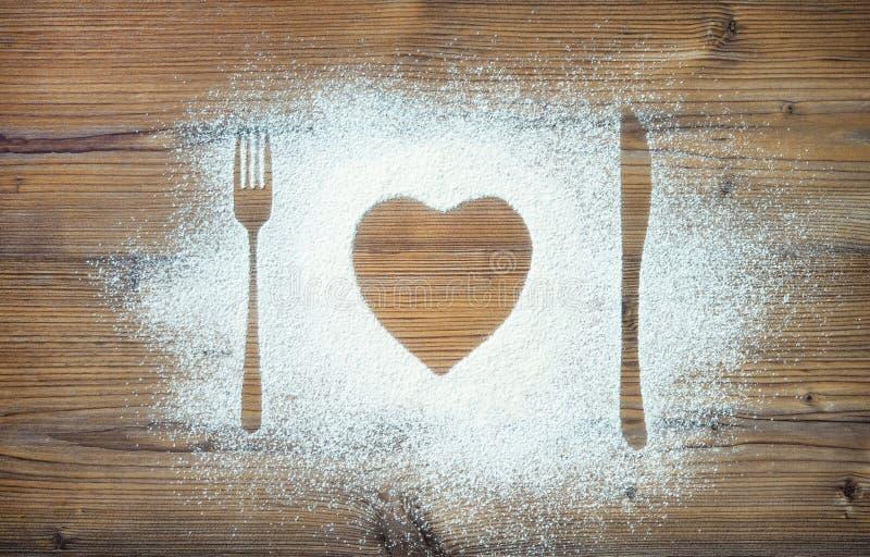 Δίκρανο, μαχαίρι και πιάτο στη μορφή καρδιών, αλεύρι που ψεκάζεται γύρω από την περικοπή στοκ εικόνα