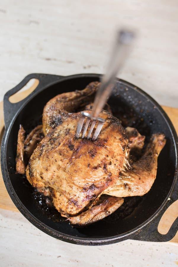 Δίκρανο στο defocus στην τηγανισμένη σχάρα κοτόπουλου στο τηγάνισμα του τηγανιού σε έναν ελαφρύ ξύλινο πίνακα στοκ φωτογραφία