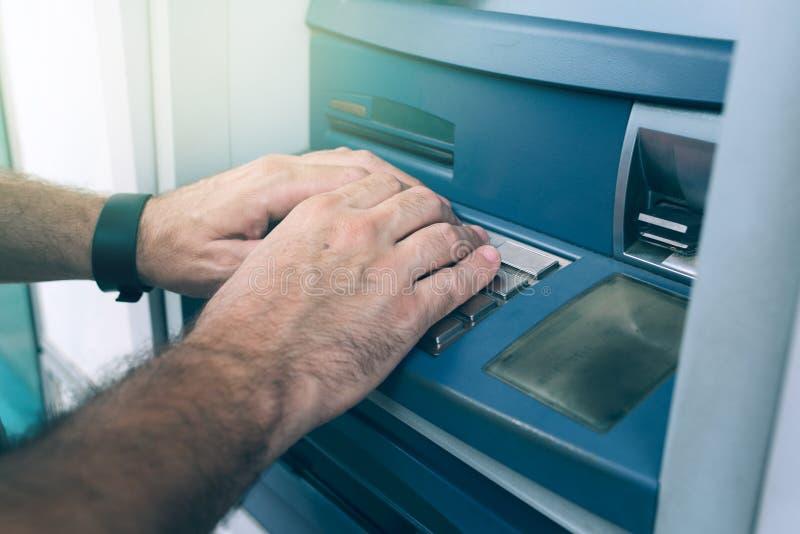 Δίνει την ΚΑΡΦΙΤΣΑ δακτυλογράφησης στη μηχανή του ATM στοκ φωτογραφία