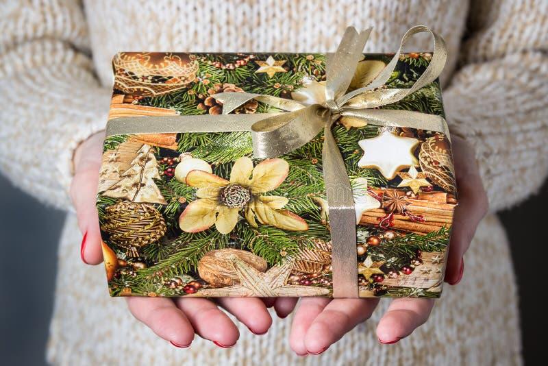 Δίνοντας ένα δώρο, χειροποίητο παρόν που τυλίγεται στο έγγραφο στενός κόκκινος χρόνος Χριστουγέννων ανασκόπησης επάνω στοκ φωτογραφία