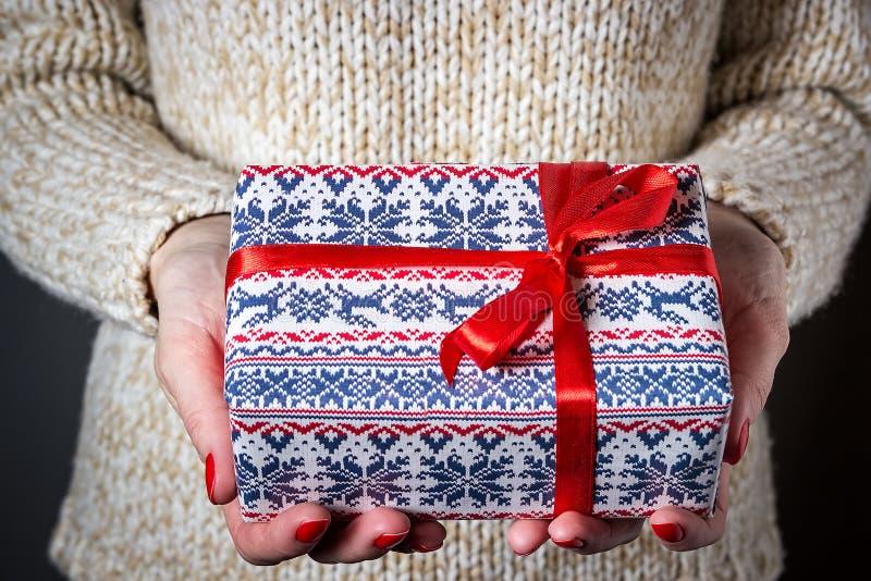 Δίνοντας ένα δώρο, χειροποίητο παρόν που τυλίγεται στο έγγραφο στενός κόκκινος χρόνος Χριστουγέννων ανασκόπησης επάνω στοκ φωτογραφία με δικαίωμα ελεύθερης χρήσης