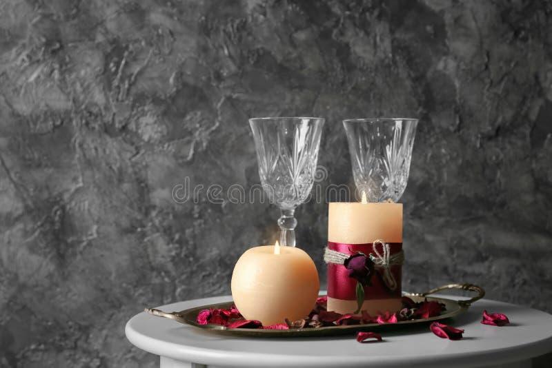 Δίσκος μετάλλων με το κάψιμο των κεριών κεριών, των γυαλιών και των πετάλων λουλουδιών στον πίνακα στοκ εικόνες με δικαίωμα ελεύθερης χρήσης