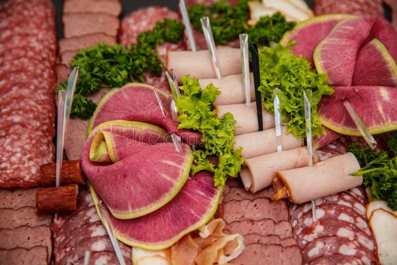 Δίσκος τροφίμων με το εύγευστο σαλάμι, κομμάτια του τεμαχισμένου ζαμπόν, λουκάνικο, σαλάτα - πιατέλα κρέατος με την επιλογή στοκ φωτογραφία