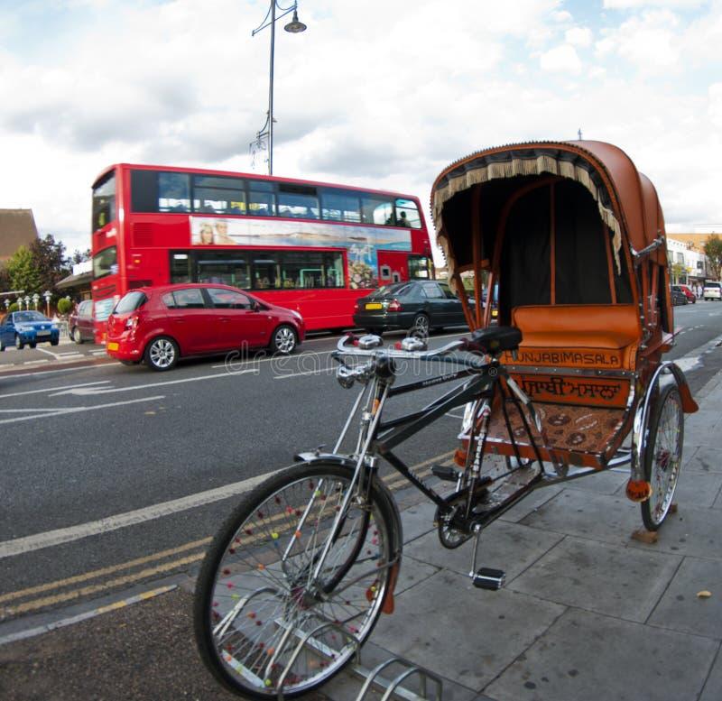 Δίτροχος χειράμαξα και ένα κόκκινο διπλό λεωφορείο καταστρωμάτων στο Λονδίνο στοκ φωτογραφία με δικαίωμα ελεύθερης χρήσης