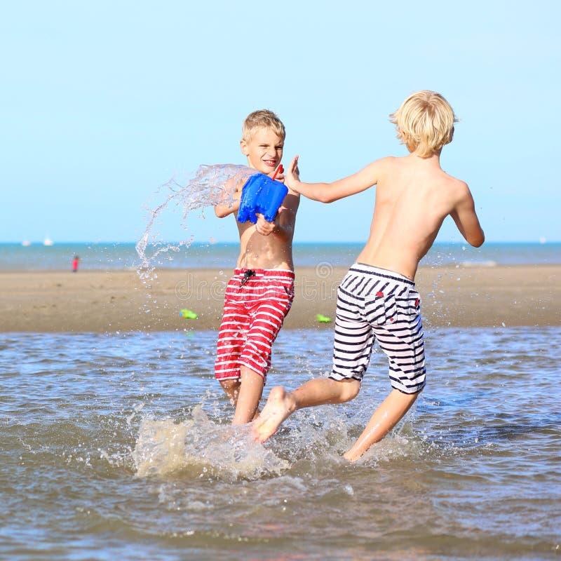 Δίδυμοι αδερφοί που παίζουν στην παραλία στοκ φωτογραφίες