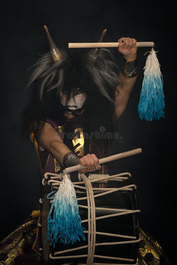 Δαίμονας από την ιαπωνική μυθολογία Πορτρέτο ενός καλλιτέχνη ντράμερ Taiko σε περούκα με κέρατα και δαιμονικό τύμπανο για μακιγιά στοκ εικόνες