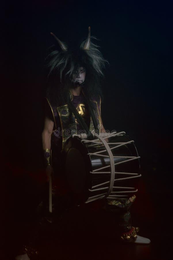 Δαίμονας από την ιαπωνική μυθολογία, πορτραίτο με πλήρη επιδεξιότητα σε ένα σκοτάδι Ντράμερ Taiko με περούκα και μάσκα δαίμονα στοκ εικόνα