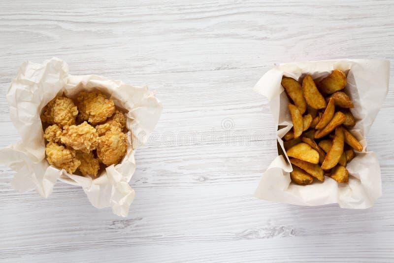 Δαγκώματα κοτόπουλου και σφήνες πατατών σε ένα άσπρο ξύλινο υπόβαθρο, τοπ άποψη r στοκ εικόνες