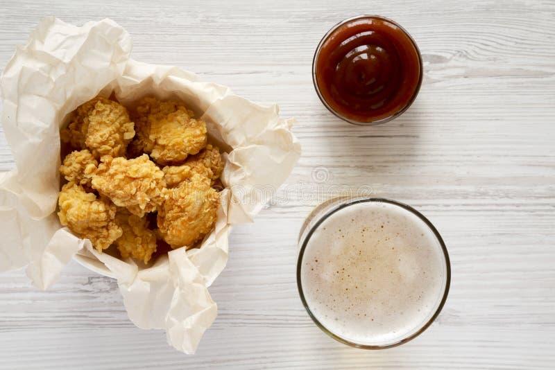 Δαγκώματα κοτόπουλου σε ένα κιβώτιο εγγράφου, μια σάλτσα σχαρών και ένα ποτήρι της μπύρας σε ένα άσπρο ξύλινο υπόβαθρο, τοπ άποψη στοκ εικόνες με δικαίωμα ελεύθερης χρήσης
