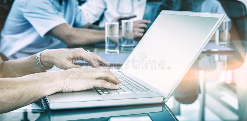 Δακτυλογράφηση γιατρών στο πληκτρολόγιο με την ομάδα της πίσω στοκ εικόνες με δικαίωμα ελεύθερης χρήσης