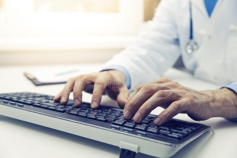 Δακτυλογράφηση γιατρών στο πληκτρολόγιο υπολογιστών στην αρχή σε απευθείας σύνδεση consultatio στοκ φωτογραφία