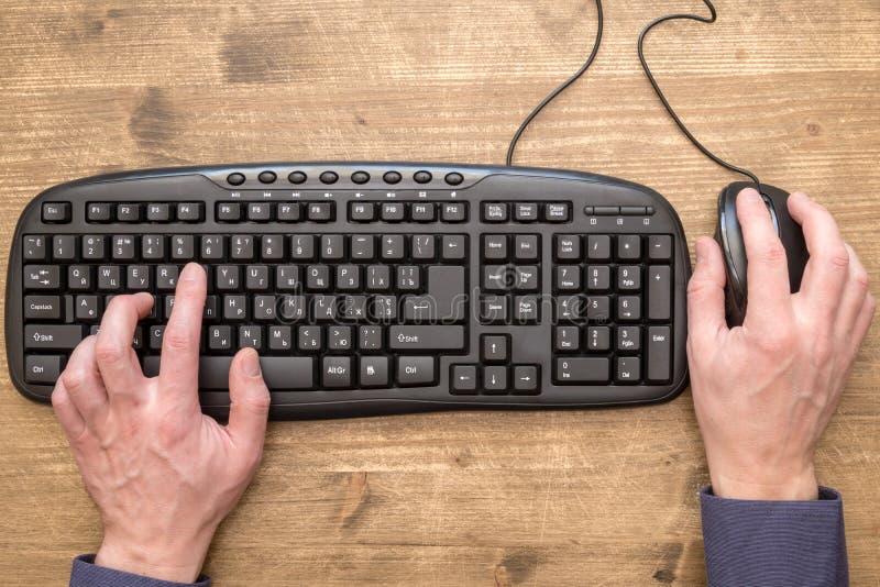 Δακτυλογράφηση χεριών επιχειρηματιών στο πληκτρολόγιο με το ποντίκι στοκ εικόνα