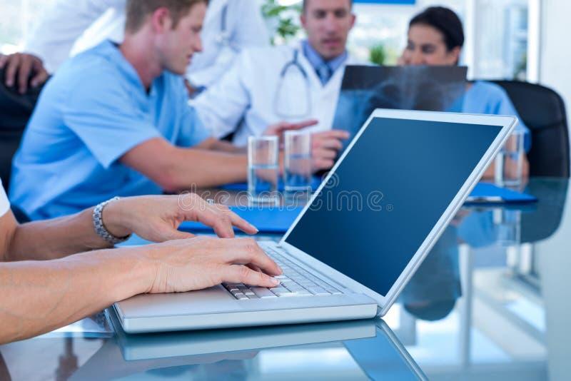 Δακτυλογράφηση γιατρών στο πληκτρολόγιο με την ομάδα της πίσω στοκ εικόνες